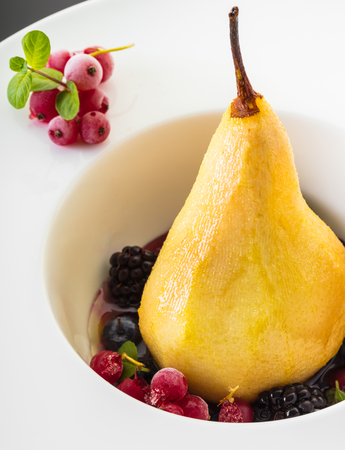 dessert, baked pear in honey syrup with berries Stock Photo