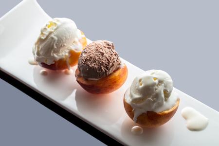 Dessert ice cream on peach, dark background with reflection Stock Photo