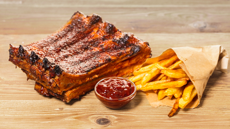 grilled ribs with fries and sauce on a wooden background Фото со стока
