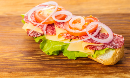 sandwich with salami, cheese and vegetables on a wooden background Stock Photo