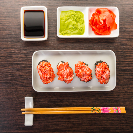 Japanese food, spicy gunkan roll on wooden background