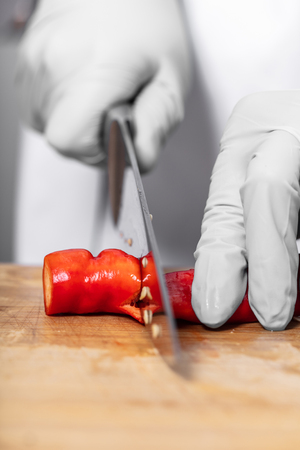 hand cutting hot chili peppers on a wooden board