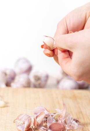 Person peeling garlic cloves closeup