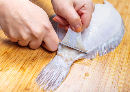 cook cutting fish flounder, female hands closeup Stock Photo