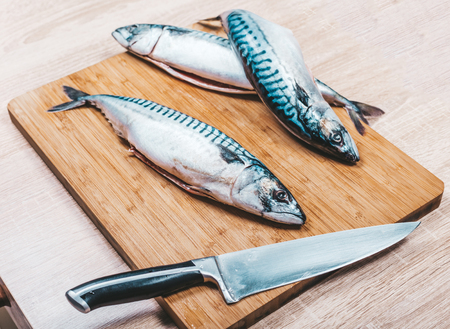 raw mackerel fish on wooden cutting board with a knife
