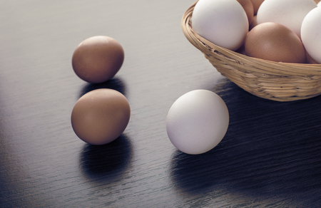 chicken eggs in a wicker bowl on a wooden background
