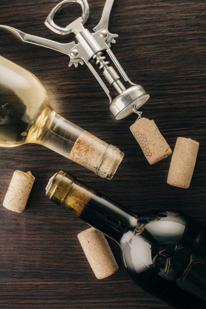 bottles of wine and corkscrew on wooden background