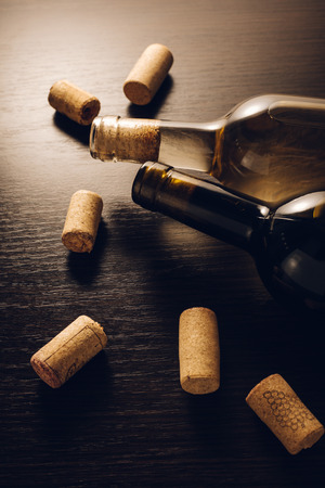 bottles of wine and corks on wooden background