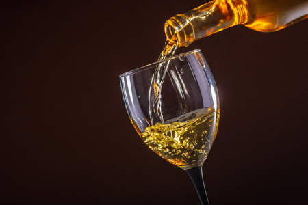 white wine pouring glass on brown background