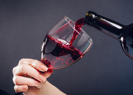 bicchiere di vino rosso che versa su sfondo nero Archivio Fotografico