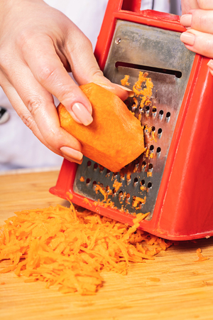 cook rubs carrots on a grater, preparation for cooking