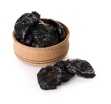prunes in a wooden bowl on white isolated background