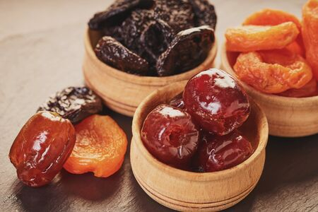 assorted dried fruits in wooden bowls on a table