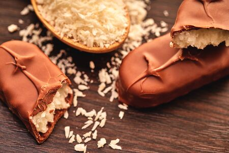 chocolate bar with coconut flakes on a wooden background