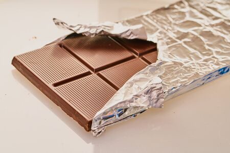 chocolate bar in foil on a white background Stockfoto