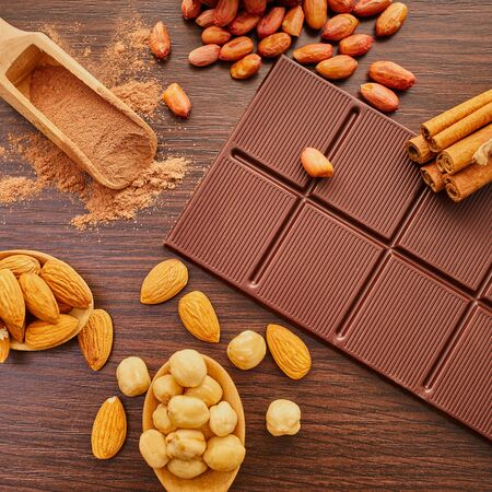 chocolate bar and nuts on wooden background