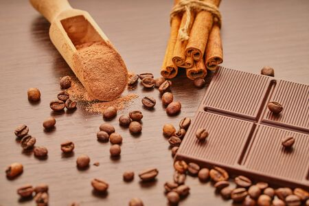 chocolate bar and coffee beans on wooden background
