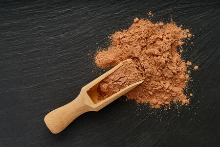 cocoa powder in a wooden scoop on black background