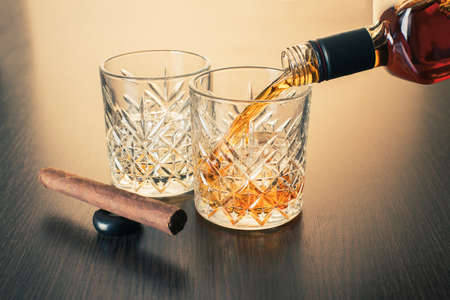 whiskey is poured into a glass from bottle on wooden background