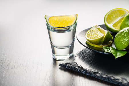 alcoholic drink in a glass with lime on dark wooden background