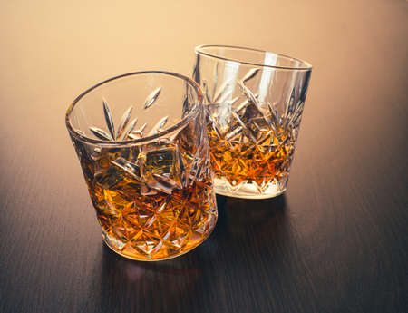 alcoholic drink, whiskey in glasses on brown wooden background 免版税图像