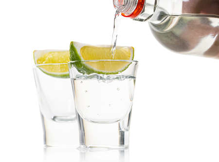 strong alcohol pouring into shot glasses on white background