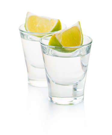 alcoholic drink in a glass with lime on white isolated background