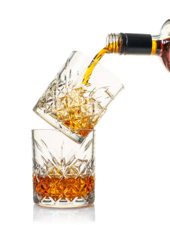 whiskey is poured into a glass from bottle on white isolated background