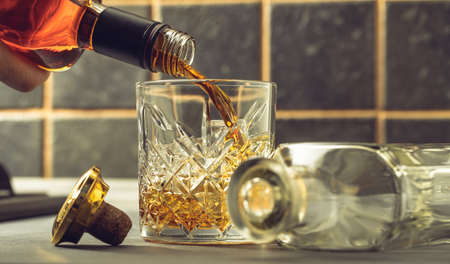 whiskey is poured into a glass from bottle 免版税图像