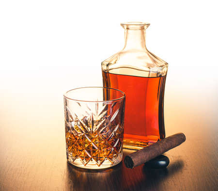 alcoholic drink, whiskey and cigar on brown wooden background 免版税图像