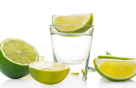 alcoholic drink in a glass with lime on white background