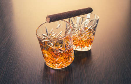 whiskey in glasses and cigar on brown wooden background