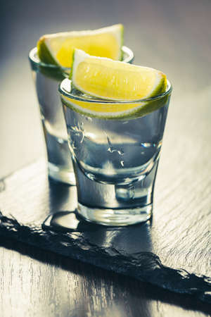 alcoholic drink in a glass with lime on dark wooden background Standard-Bild