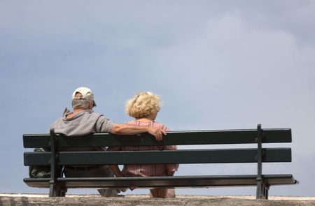 an elderly couple sitting on a bench, back, the man with one arm on the back of the bench