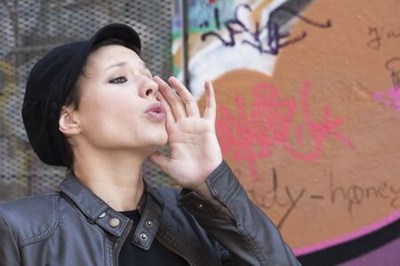 A young woman shouted, her hand to her mouth photo