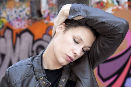 Portrait of a young woman massaging head photo