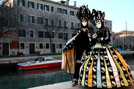 Masked man and  woman in front of a canal at the Venice Carnival photo