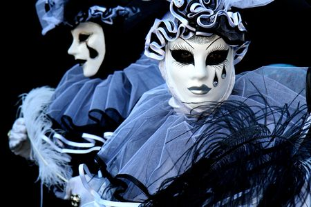 Two people dressed as Pierrot on black background, during the Venice Carnival photo