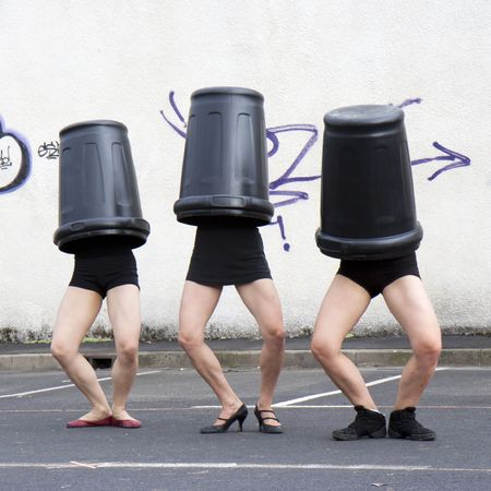Three dancers, his head in trash Stock Photo