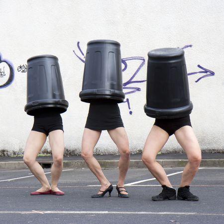 Three dancers, his head in trash Stock Photo