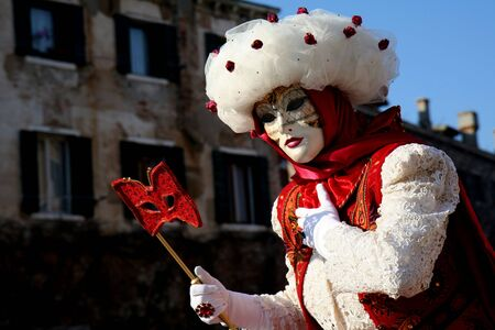 A masked woman with a red eye mask, dressed in white and red, at the Venice Carnival Stock Photo