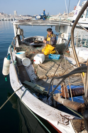 MARSEILLE, FRANCE,  MARCH 6: a fisherman, on the knees in his boat, in the Vieux-Port, tidies up his nets, on Sunday, March 6th, 2011 in Marseille, France.