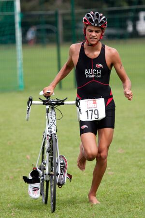 transition: AUCH, FRANCE,  SEPTEMBER 4, 2010: Auch triathlon, a male competitor barefoot  in the transition area at the end of the cycle race, on September 4th, 2010, in Auch, France. Editorial