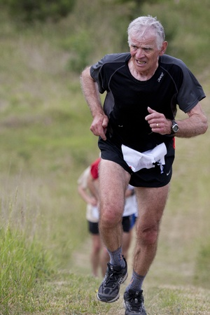 PAVIE, FRANCE - MAY 22, 2011: Senior runner grimacing at the Trail of Pavie, on May 22, 2011, in Pavie, France.