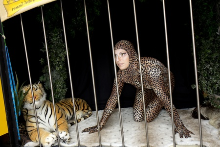 SOULAC SUR MER, FRANCE - JUNE 5, 2011: a woman locked in a cage with a tiger at the Soulac 1900 festival on june 5, in Soulac sur mer, France. Every year all the resort relives his Belle Epoque 1900 . Stock Photo - 9687320