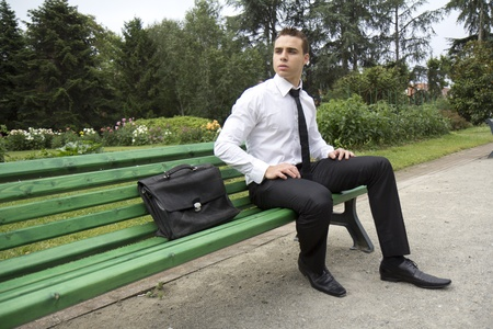look for: Young businessman sitting on a bench outdoors. It looks like he is waiting for someone. Stock Photo