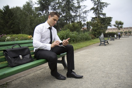 business man phone: Young business man sitting on a bench outdoors. He is consulting a mobile phone. Stock Photo