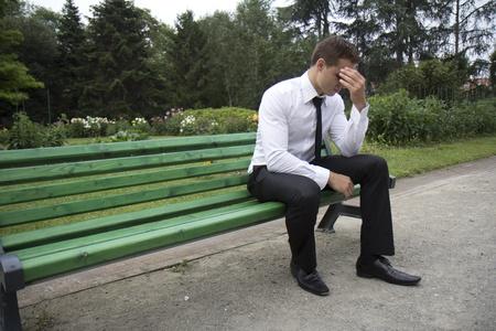 anguished: Giovane imprenditore seduto su una panchina. Sembra che lui � stanco.