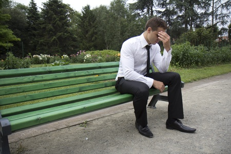 tension: Young businessman sitting on a bench. It looks like he is tired.