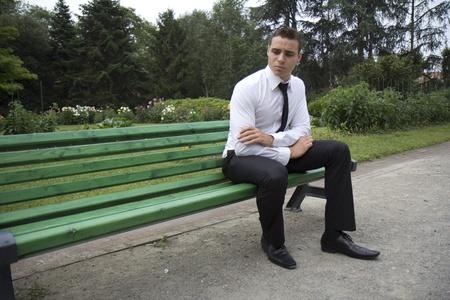 anguished: Young businessman sitting on a bench. It looks like he is anguished.